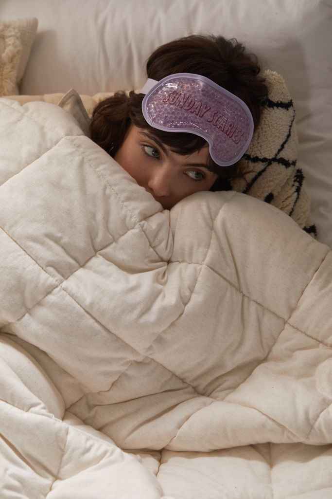 a woman lying in bed with the purple gel eye mask on