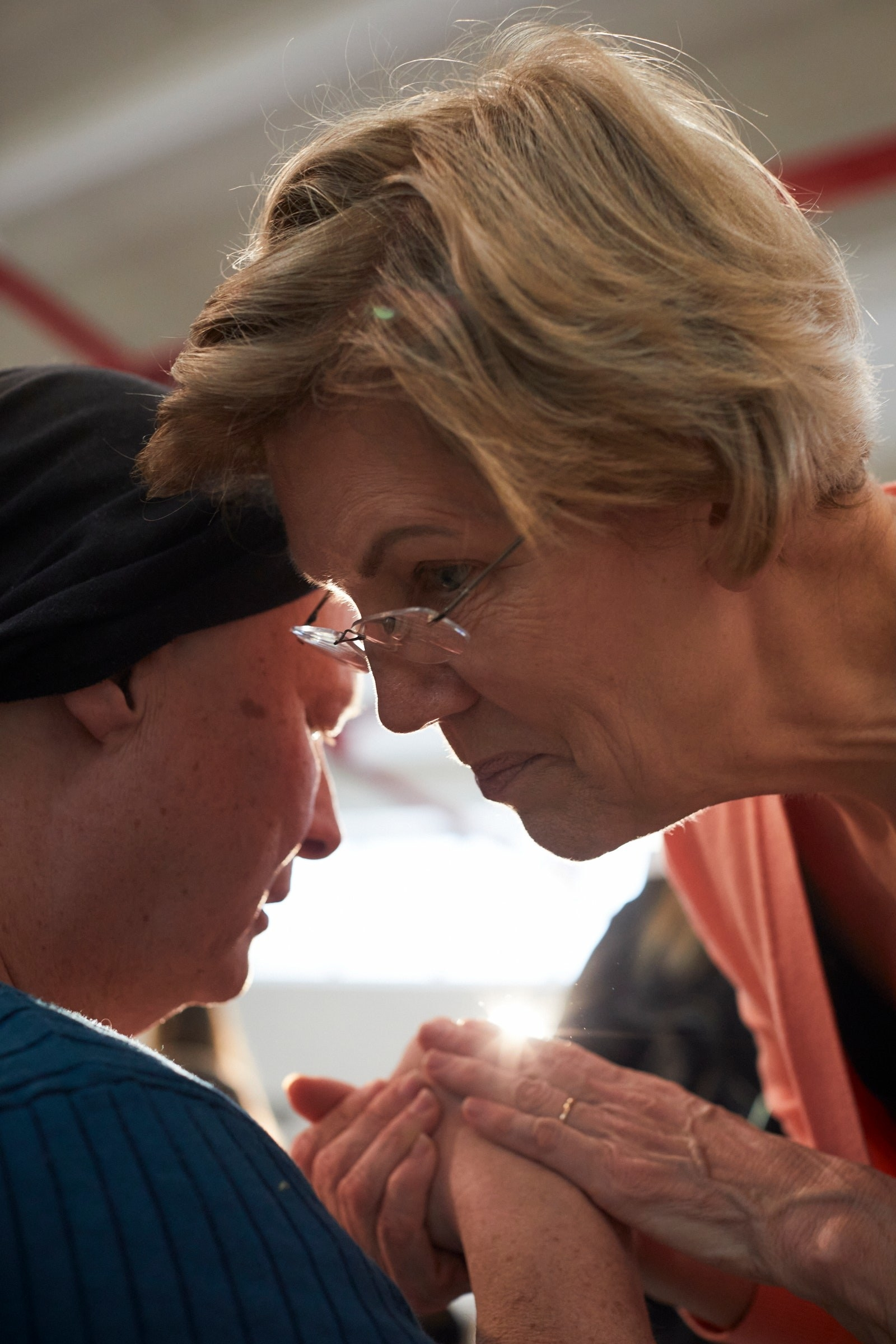 Former presidential candidate Elizabeth Warren leaning over to speak to someone, facing slightly away from the camera