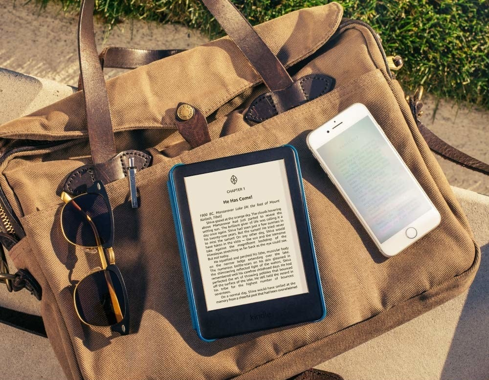 Kindle kept beside a mobile phone on top of a bag in the sunlight, clearly glare-free unlike the device beside it.