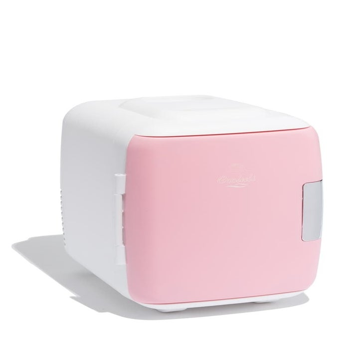 The small white fridge with a pink door