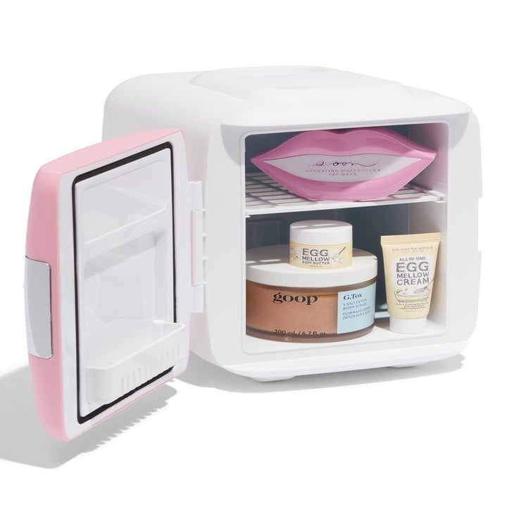 The fridge with the door open, showing the shelf inside and on the door and skincare products inside