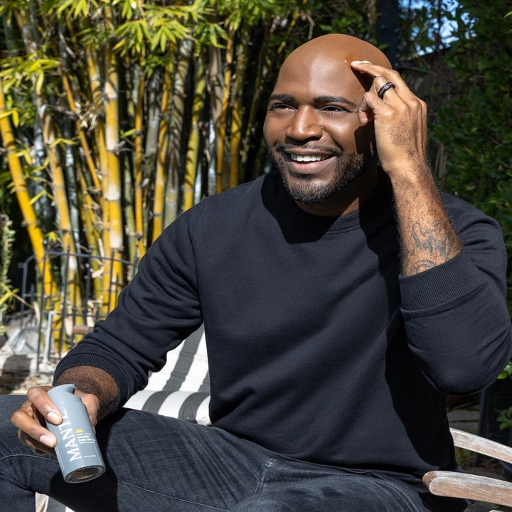 Karamo Brown holding the sunscreen and applying it to his head