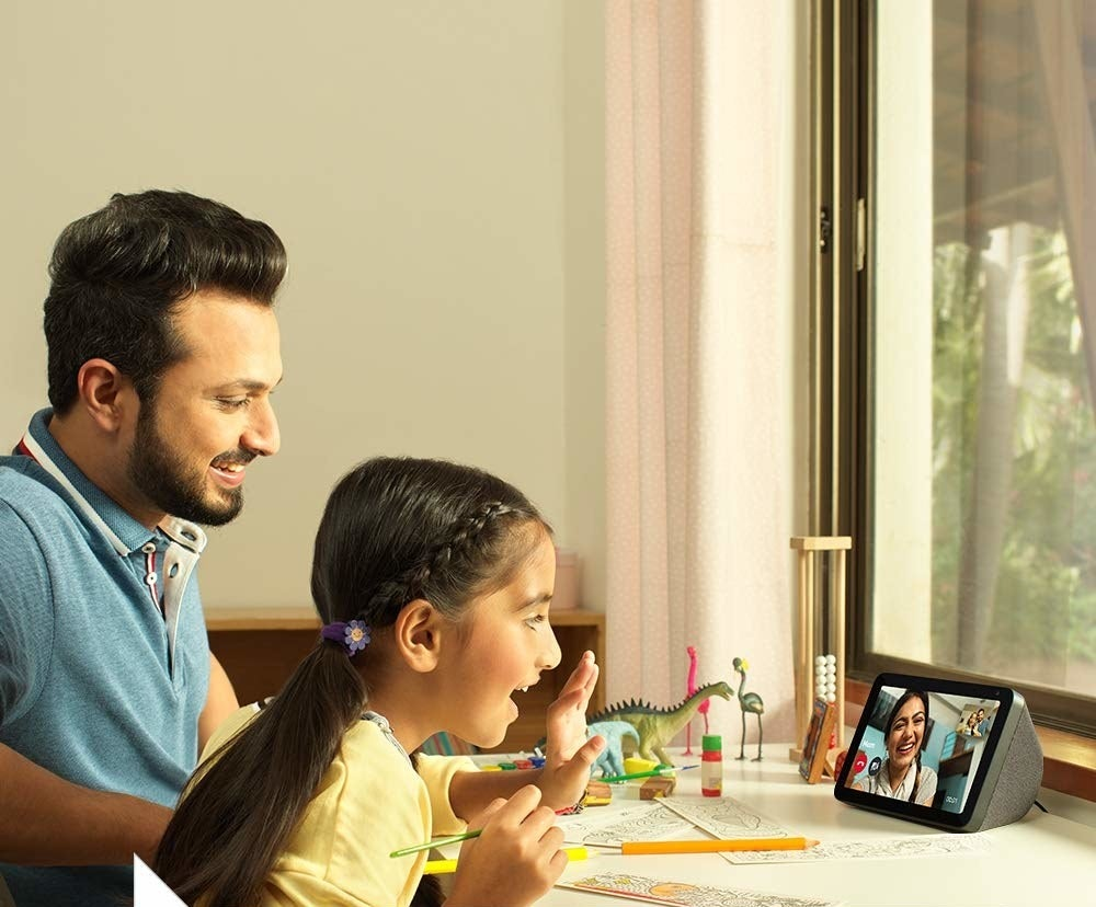 Two people talking to someone on the screen of the Echo Show 8.