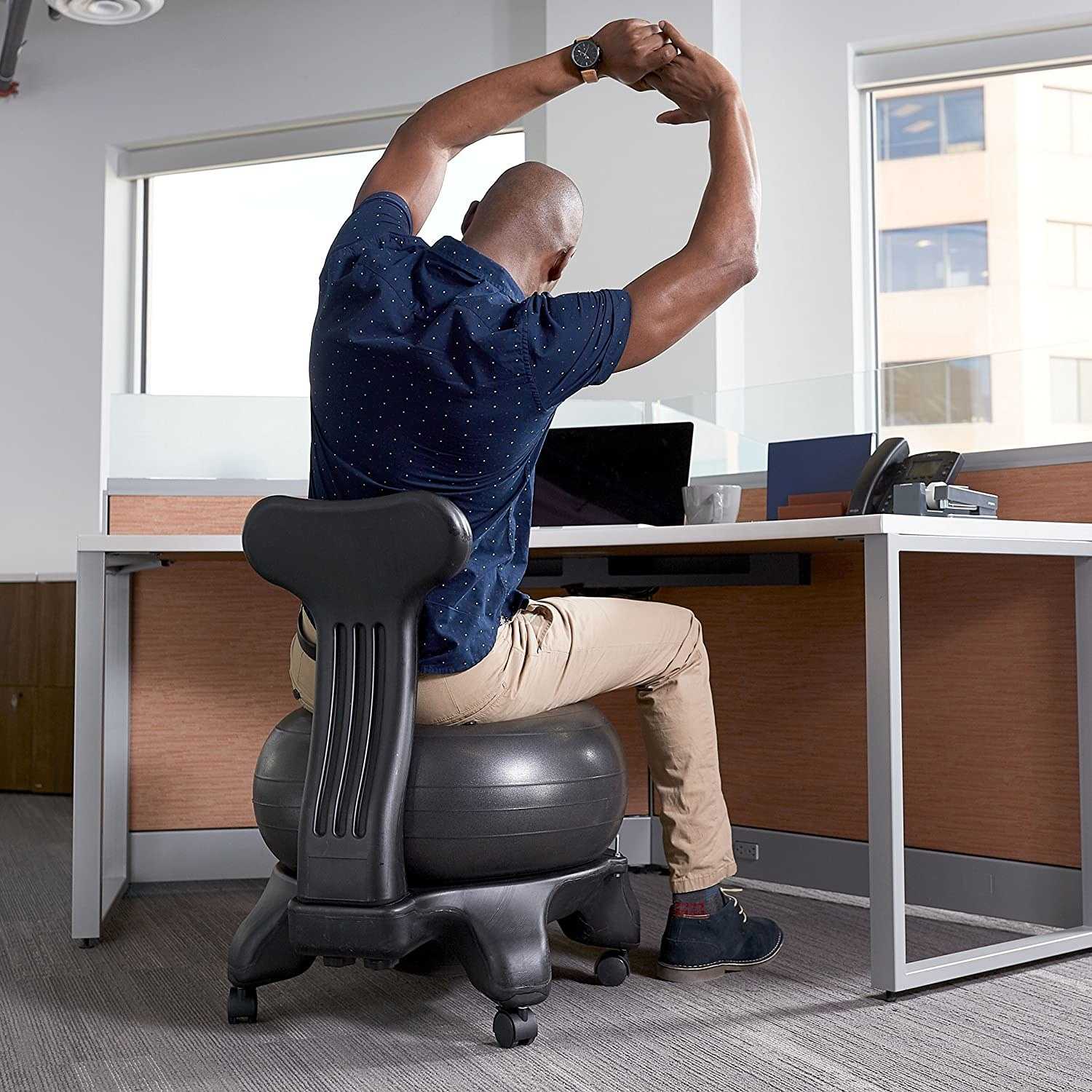 A person stretching in front of their desk while sitting on the ball chair.
