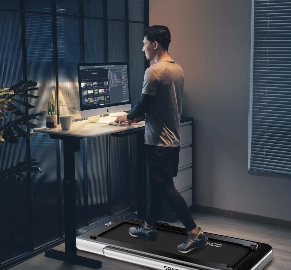 A person walking on the walking pad in front of their standing desk and working.