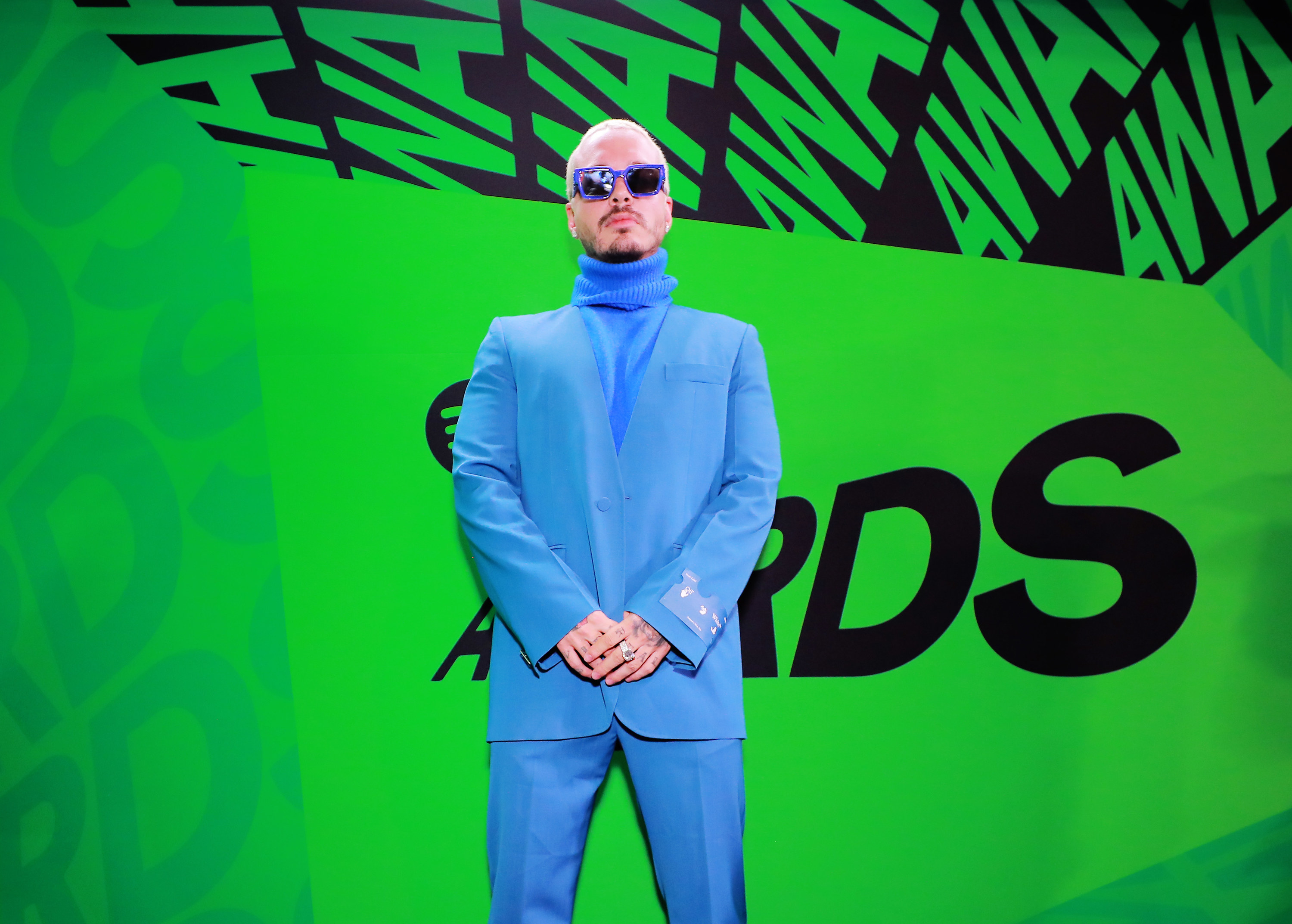 J Balvin posing in a suit and matching turtle neck at the 2020 Spotify Awards