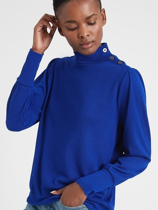 A model wearing the mock neck top in royal blue