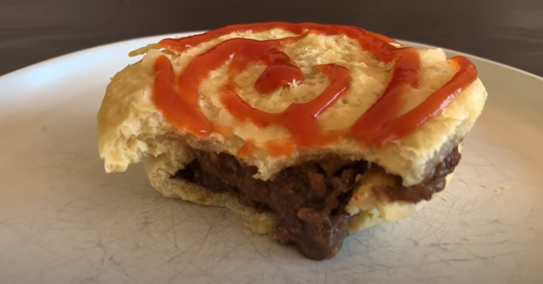 Bitten into meat pie with tomato sauce swirled on top