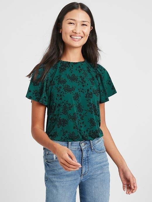 A matte jersey top in green with black floral design