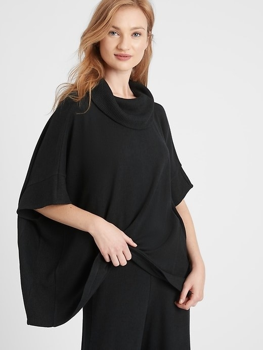 A model wearing the poncho in black