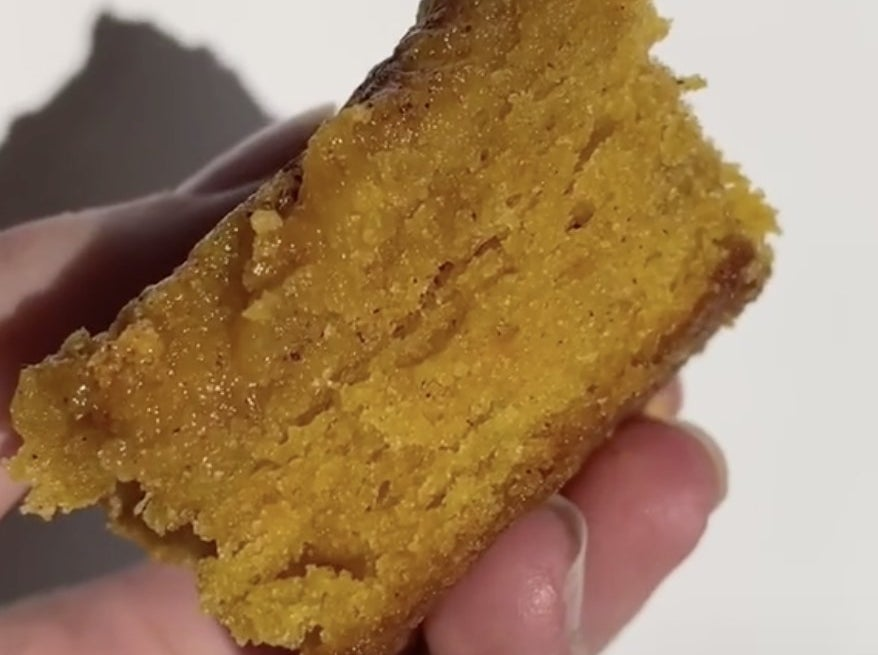A hand holding a slice of pumpkin bread