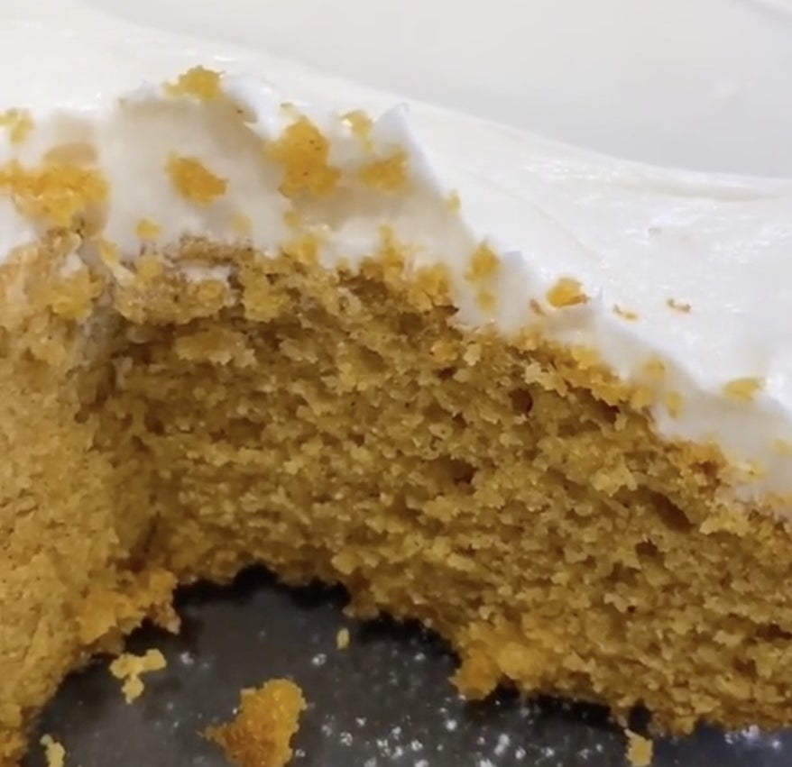 A slice of golden cake with white frosting