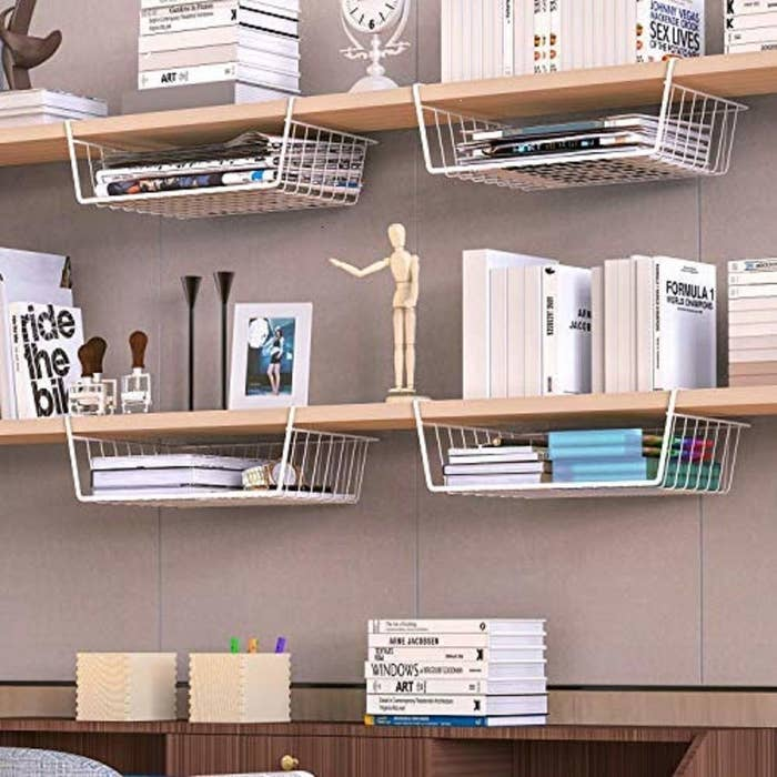 Wire storage baskets clipped on to shelves.