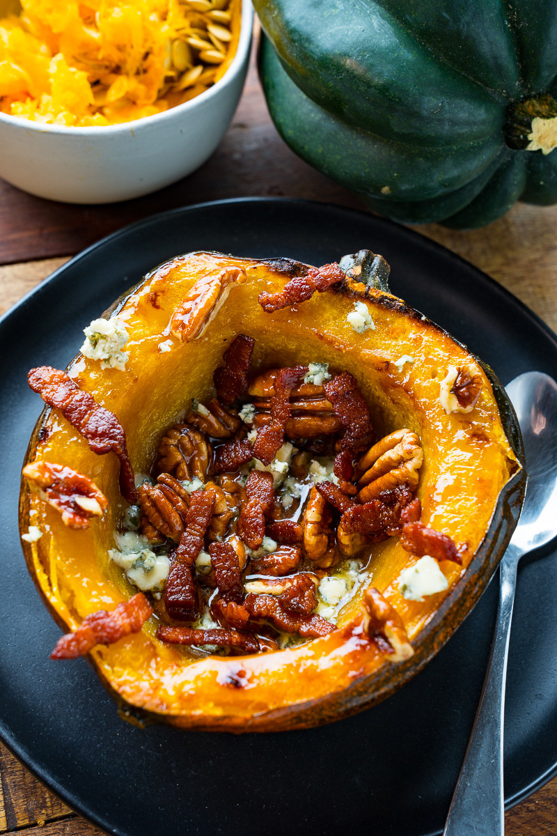 A half of an acorn squash, roasted and topped with blue cheese, pecans, and bacon.