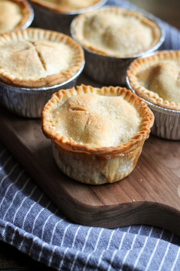 Mini apple pies cooked in cupcake holders.