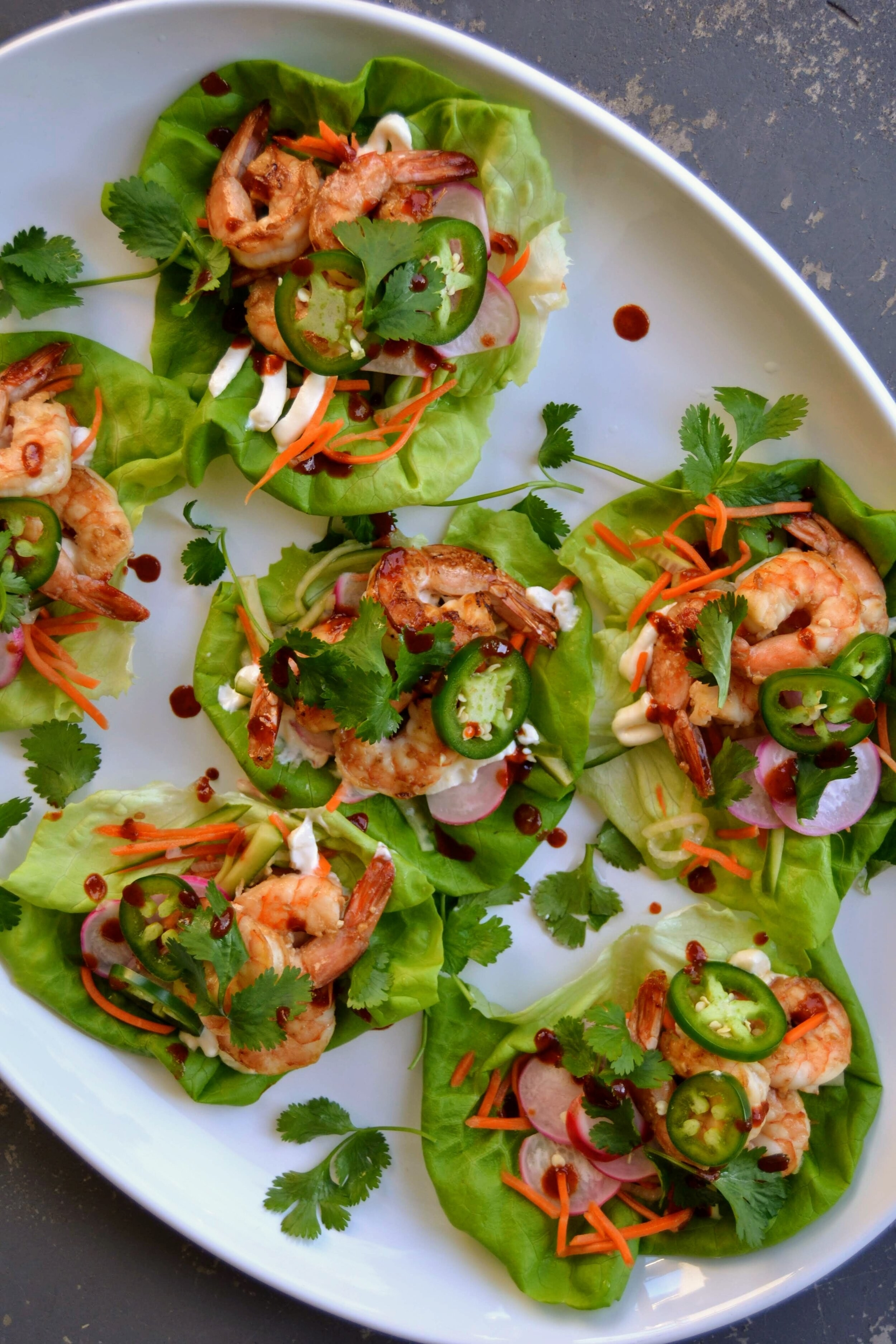 Lettuce cups filled with shrimp, radishes, carrots, jalapeño, and herbs.
