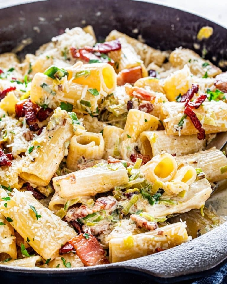 A skillet of rigatoni with bacon in a creamy leek sauce.