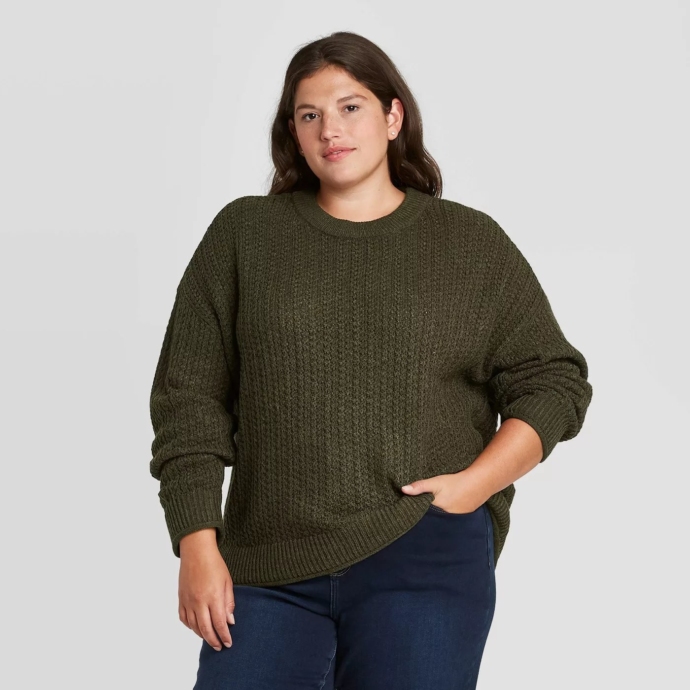 A model wearing the sweater in olive heather
