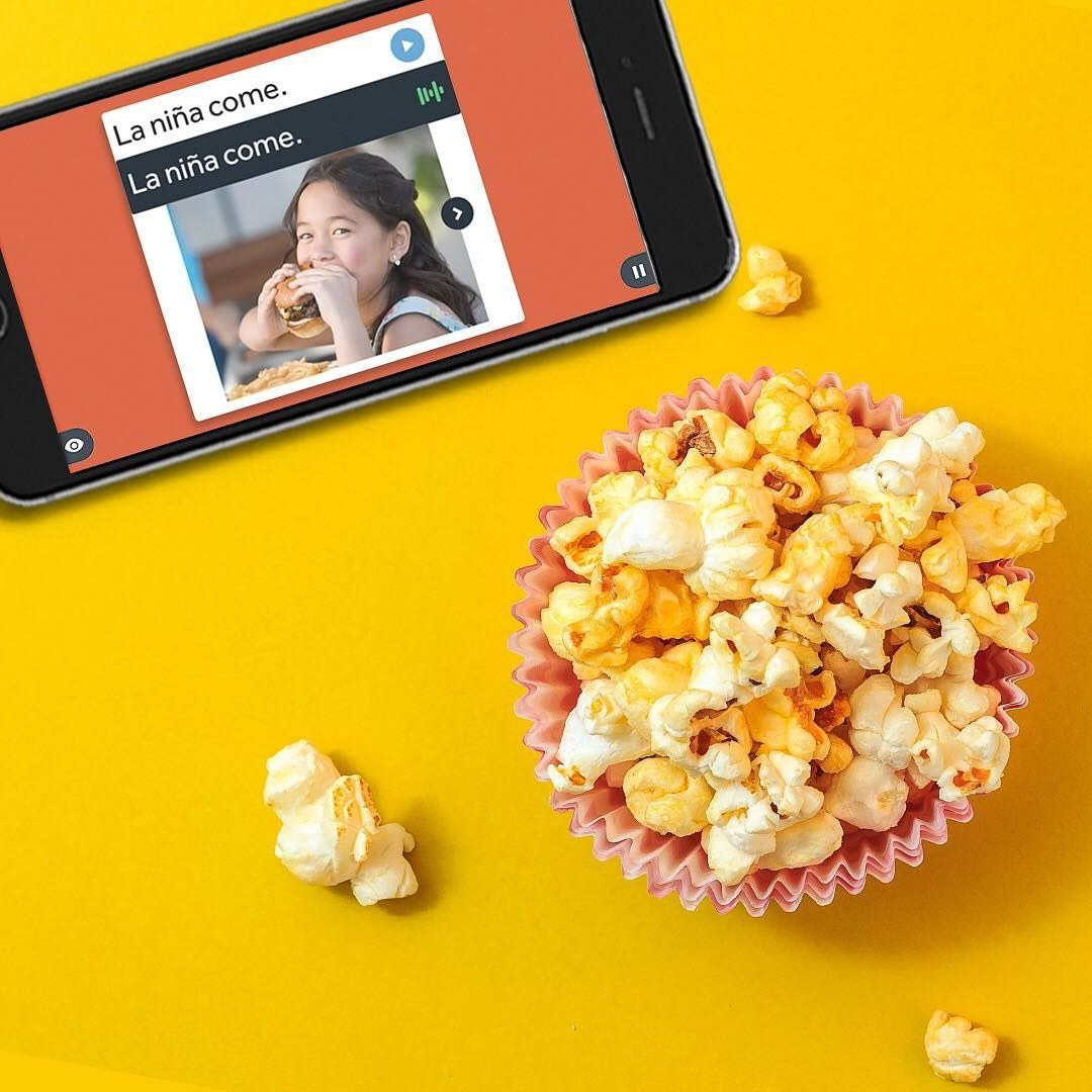 the Rosetta Stone app on a phone next to a cup of popcorn