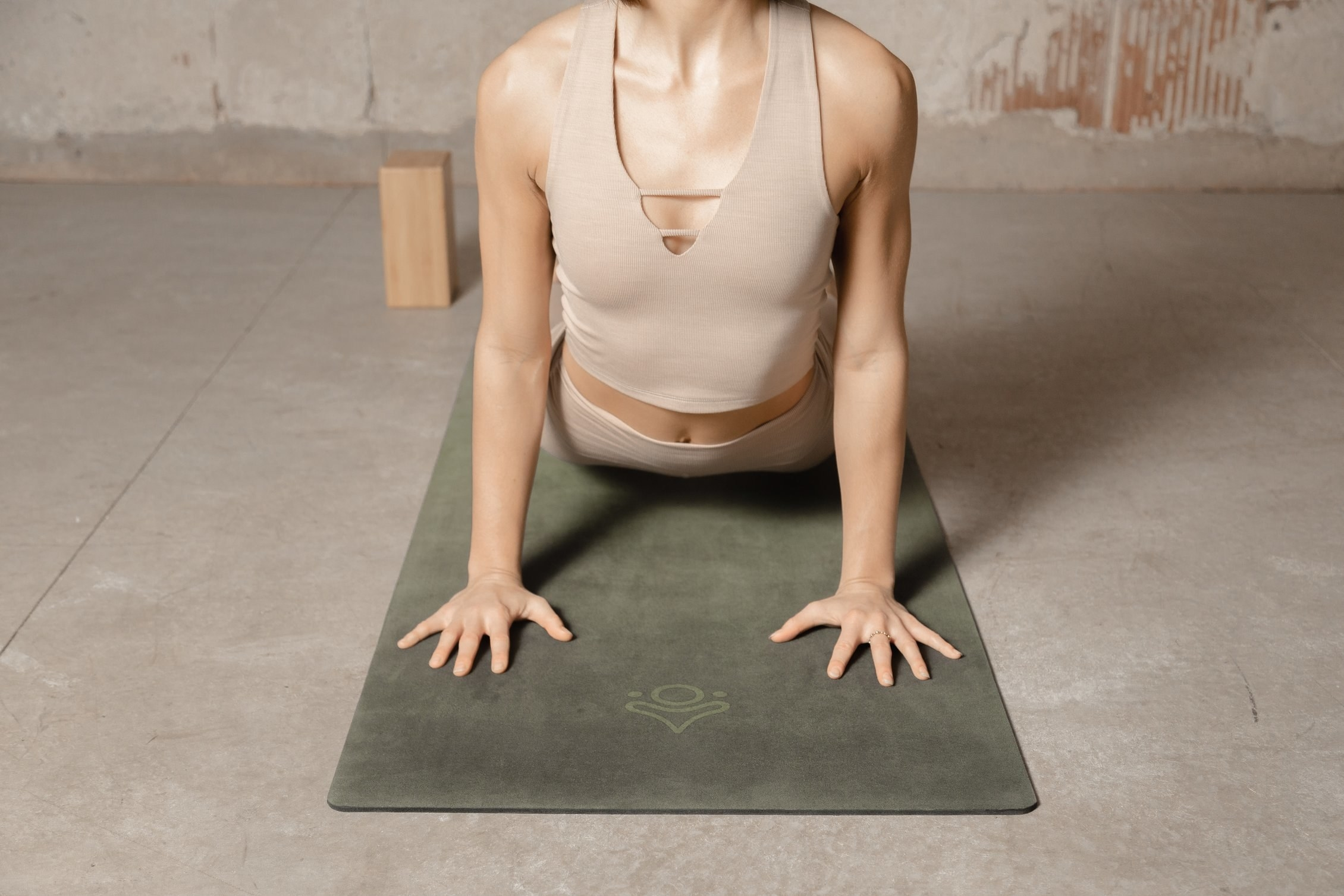 a model doing yoga on a sage green mat