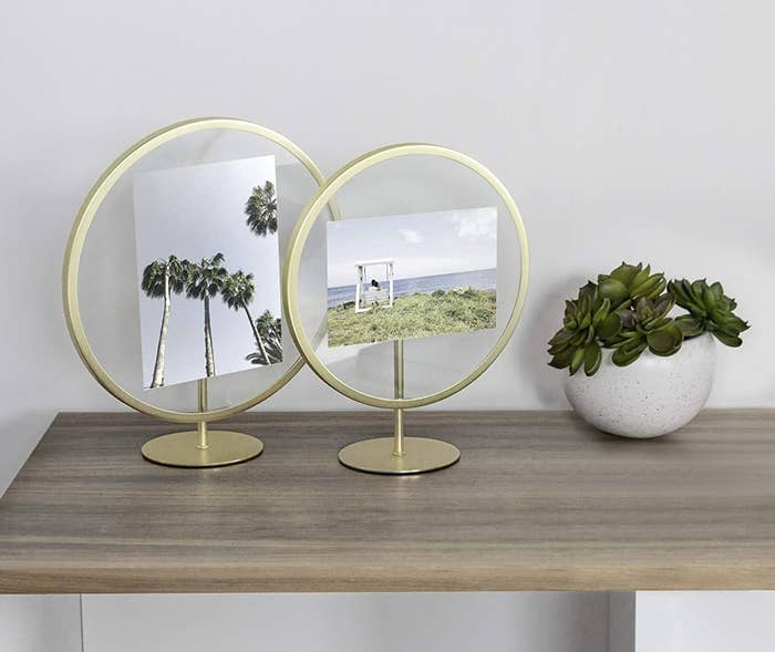 Two gold circular frames and stands with pictures in the glass center