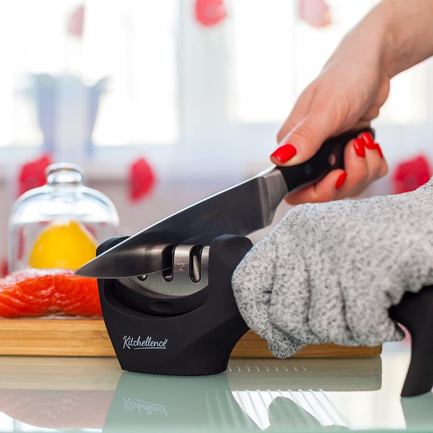 A knife being sharpened on a kitchen counter with a protective glove also being used