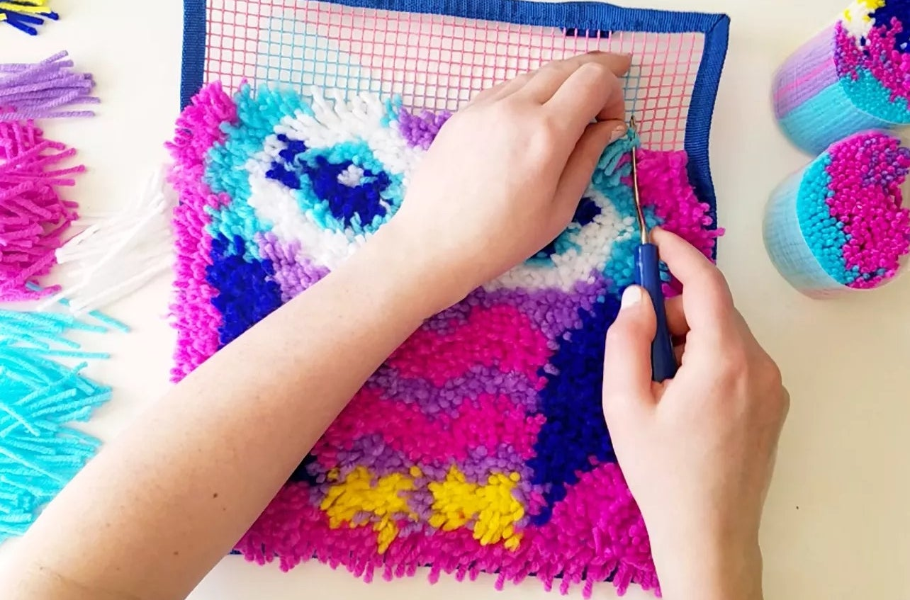 A model using the latch hook craft tool to create an owl rug