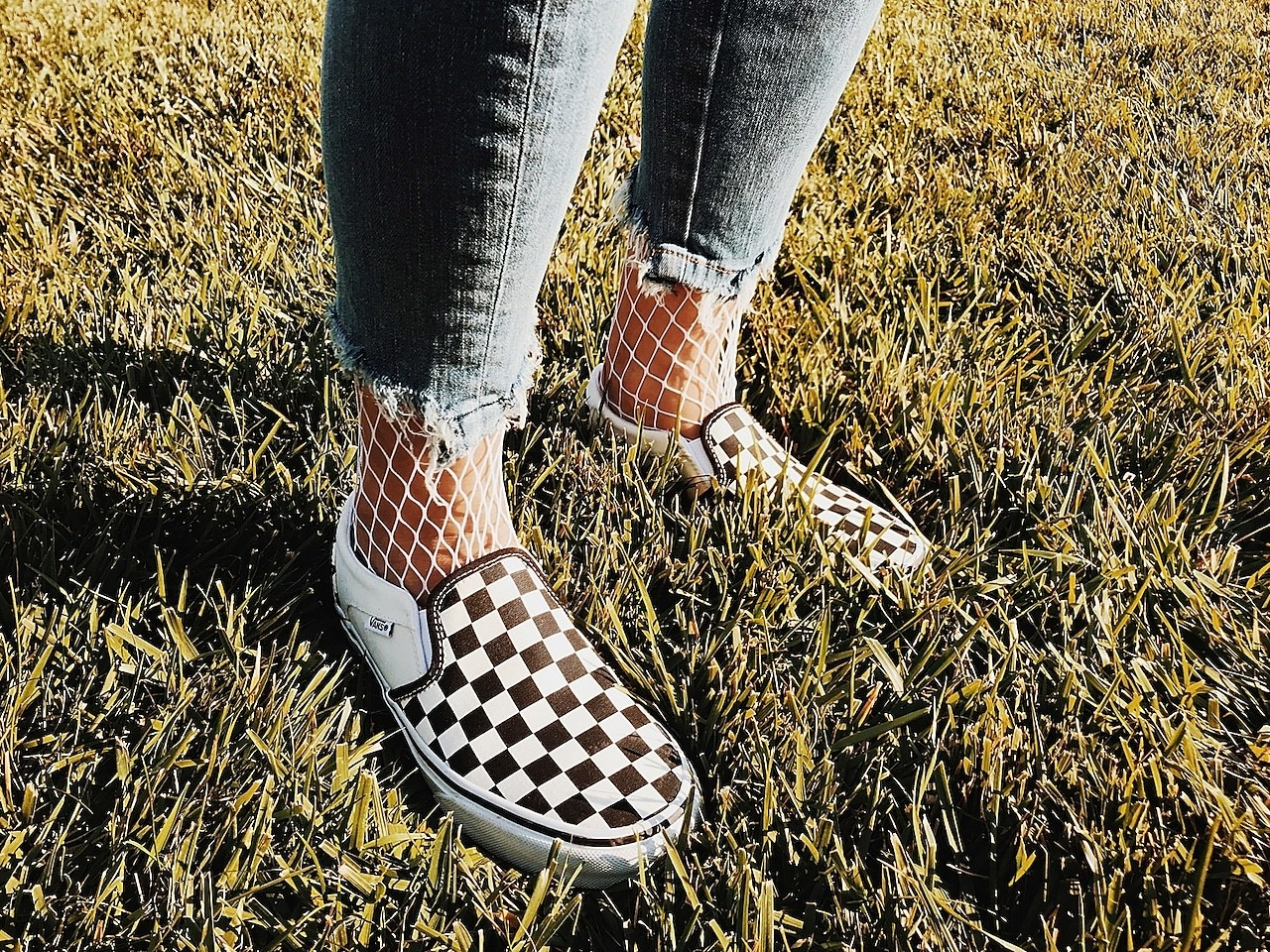 Person wearing checkered Vans slip-ons with fishnet socks