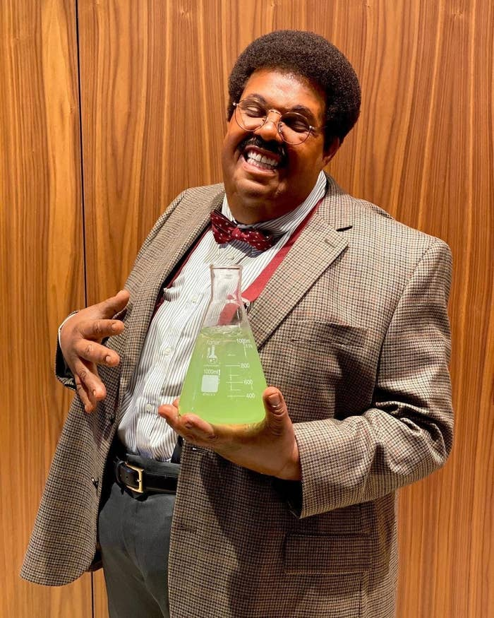 The Weeknd wearing slacks, suspenders, a jacket, and a bowtie while holding an Erlenmeyer flask filled with liquid