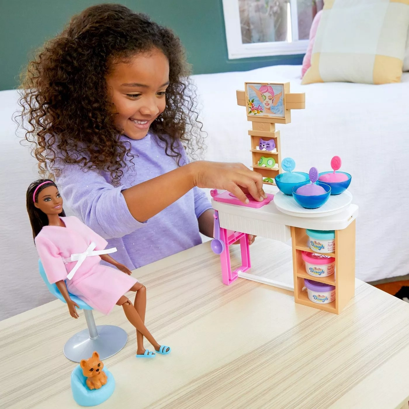 A child playing with a Barbie, her dog, and the face mask station that comes with two molds, three tubs of dough, a blemish marker, and 10 accessories