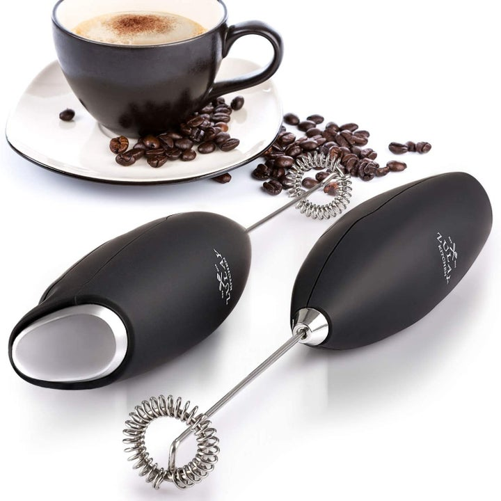 Two milk frothers beside a cup of coffee.