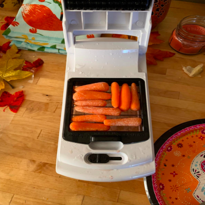 Reviewer places tiny carrots in a three-in-one veggie chopper, slicer, and spiralizer