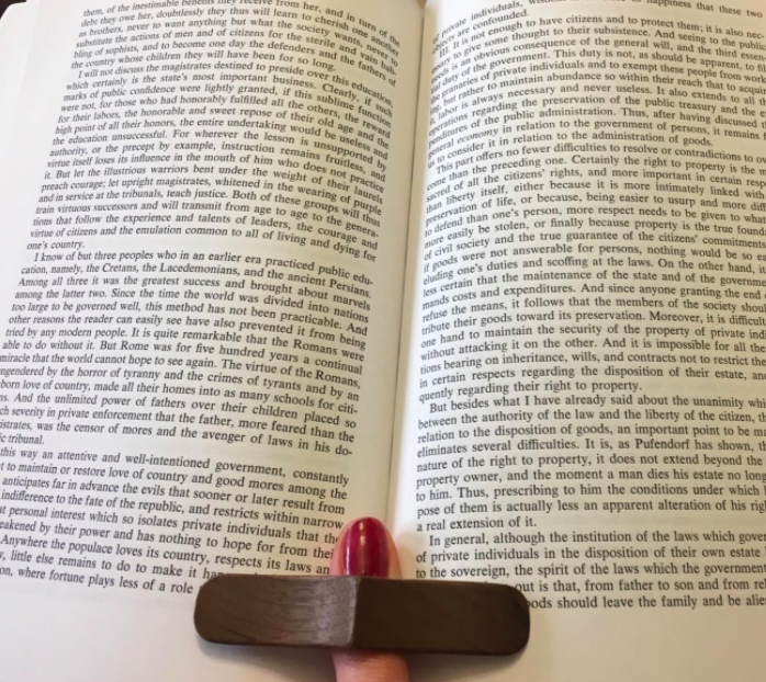 Reviewer using the book page holder to prop their book open while they read
