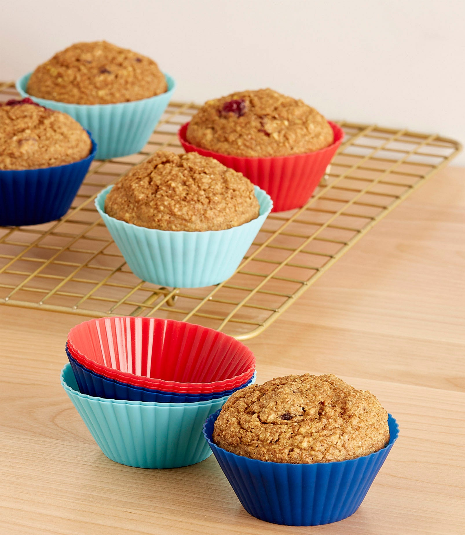 A batch of muffins in silicone baking cups cooling on a wire rack