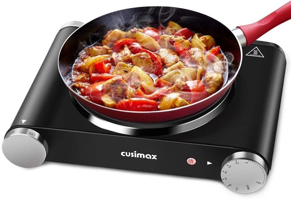 Cusimax black portable hot plate with a red pan cooking sausage and peppers on top