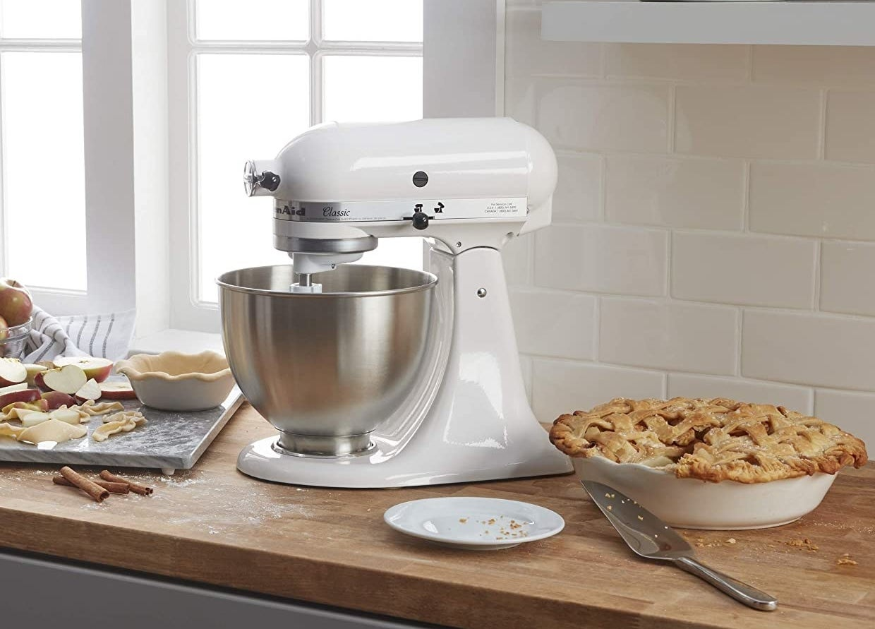 A large stand mixer on a counter top with a baked pie next to it