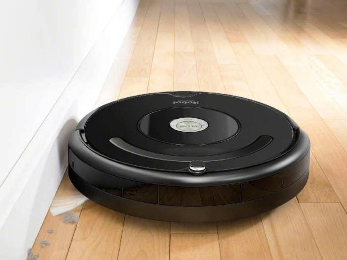 An Roomba vacuuming a hardwood floor