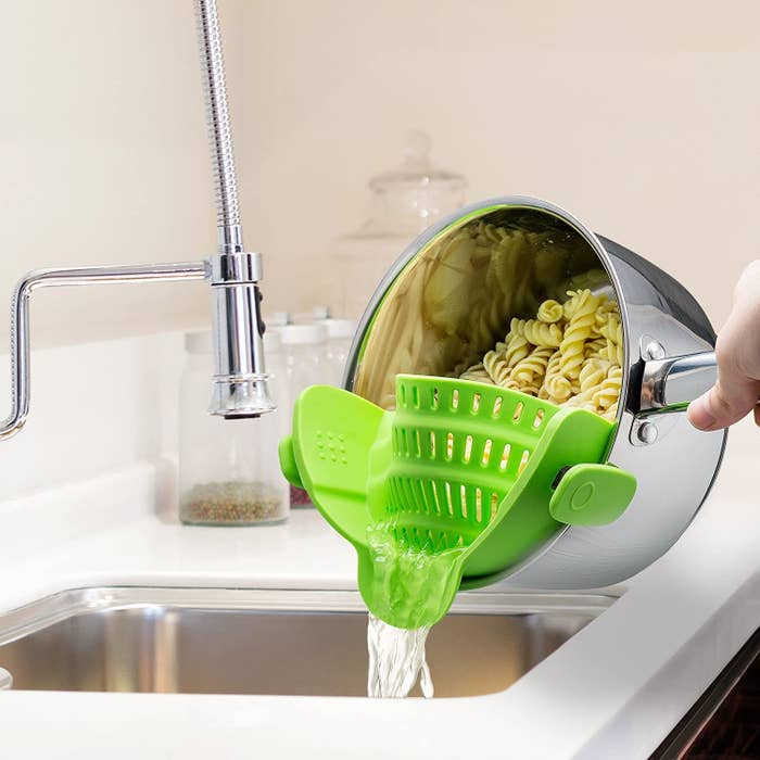 Model uses silver pot with clip-on green strainer to strain water out of a batch of pasta in a sink