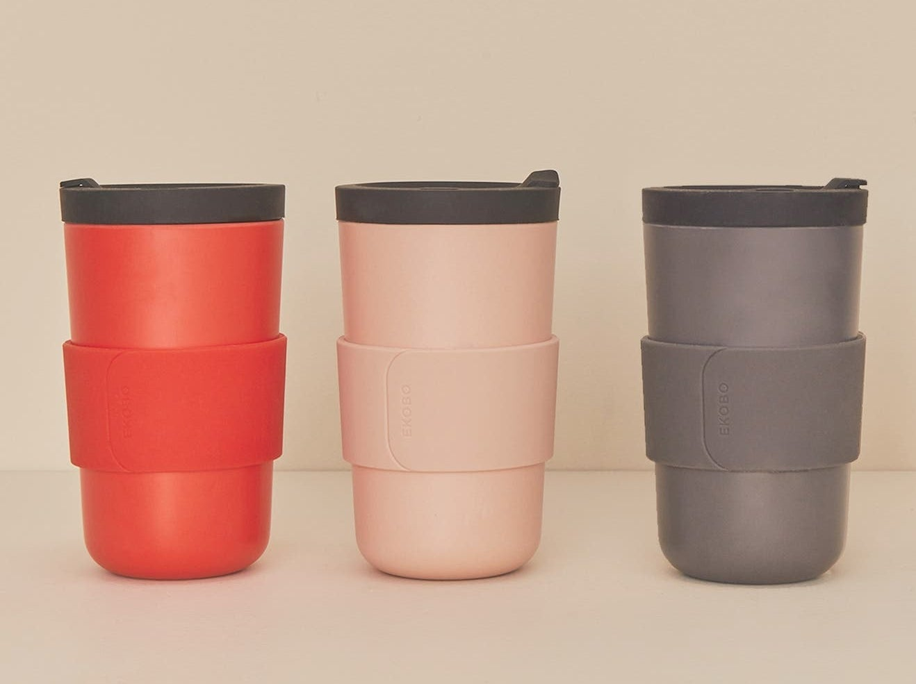 The red, light pink, and grey mugs with dark grey lids and matching colored sleeves
