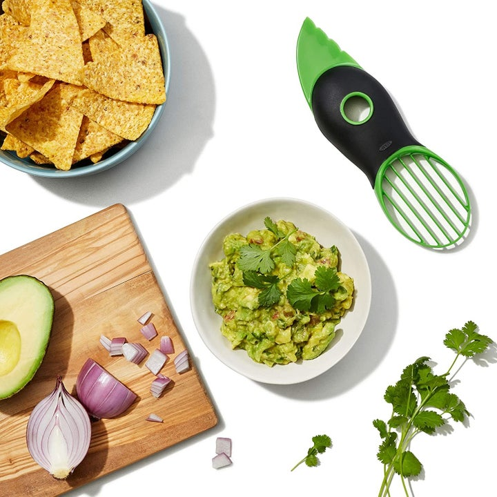 Green avocado slicer next to bowl of guacamole and sliced avocado on a cutting board
