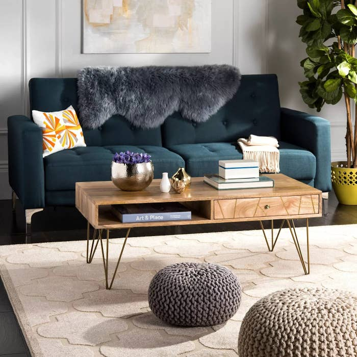 The mango-wood coffee table with iron legs, a drawer, and an open shelf