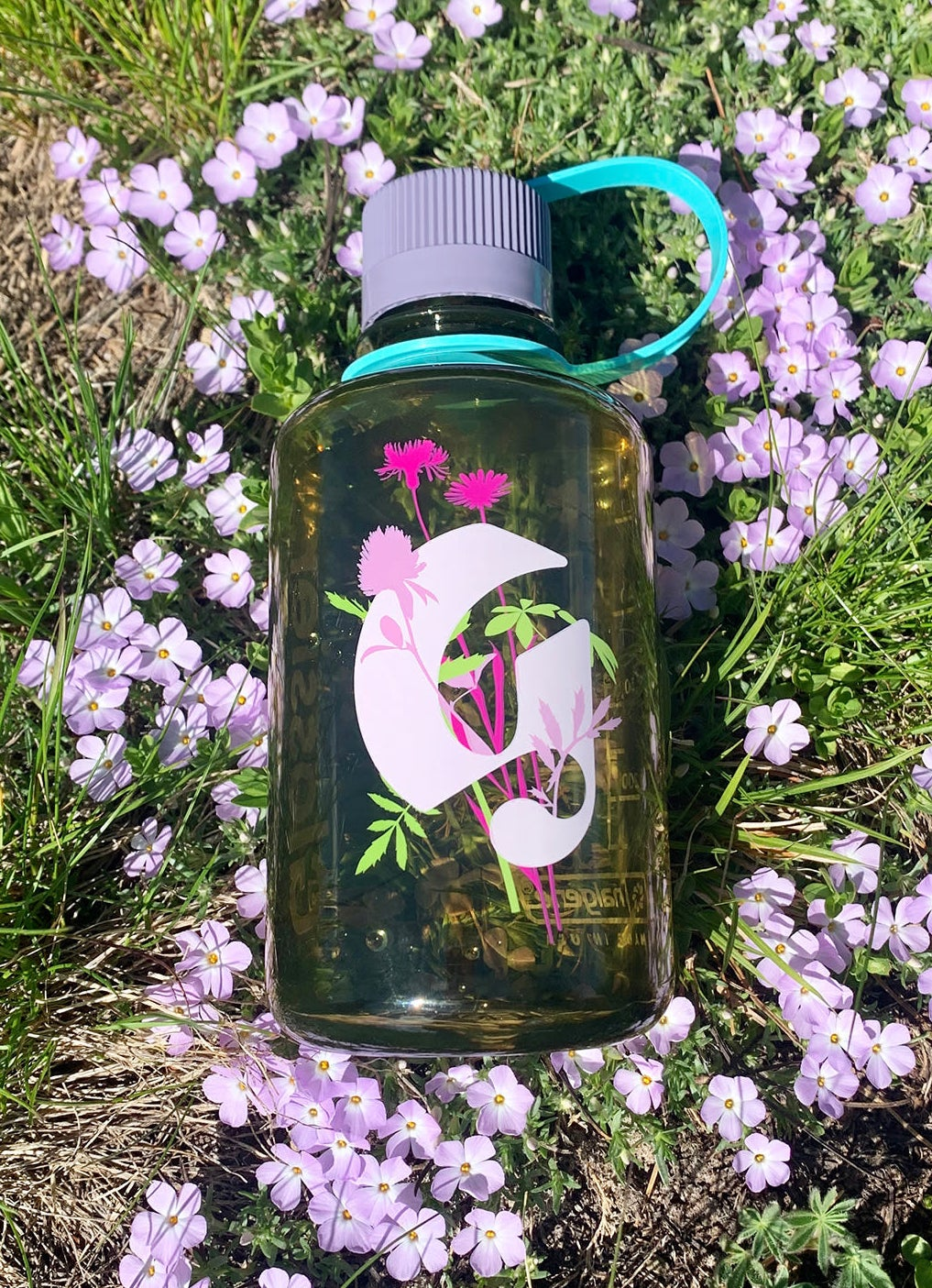 The semi-clear green water bottle with a floral Glossier g logo in pink with flowers on it on the front and grey lid with teal strap