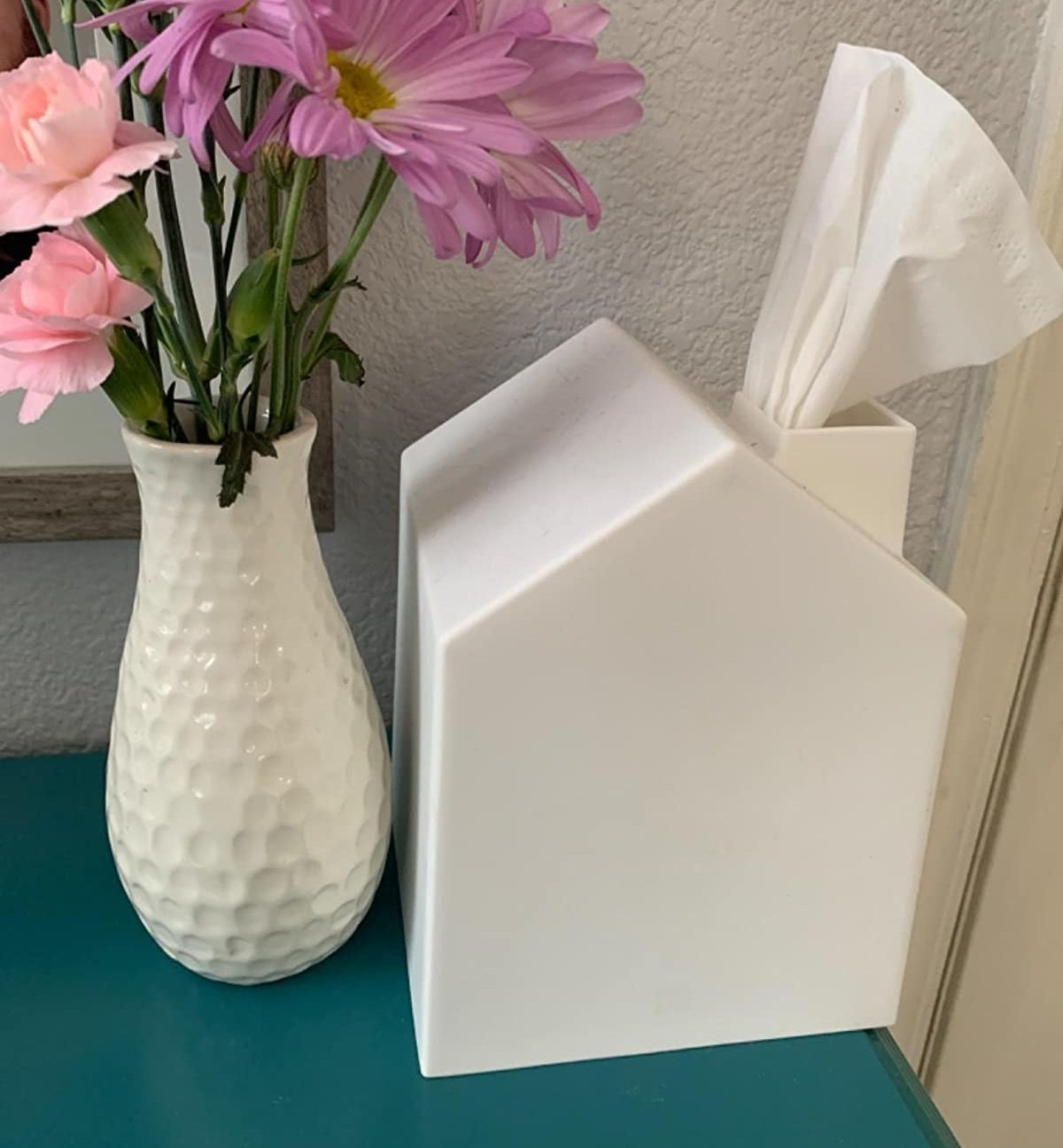 A three-dimensional house-shaped tissue holder sitting next to a vase of flowers