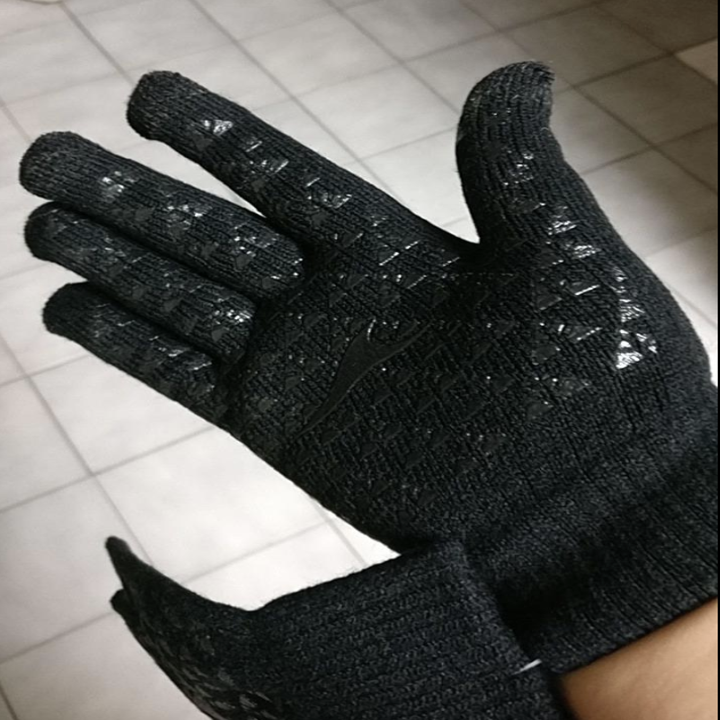 Reviewer in black gloves showing rubber grooves on inside of the hand for gripping and touch screens