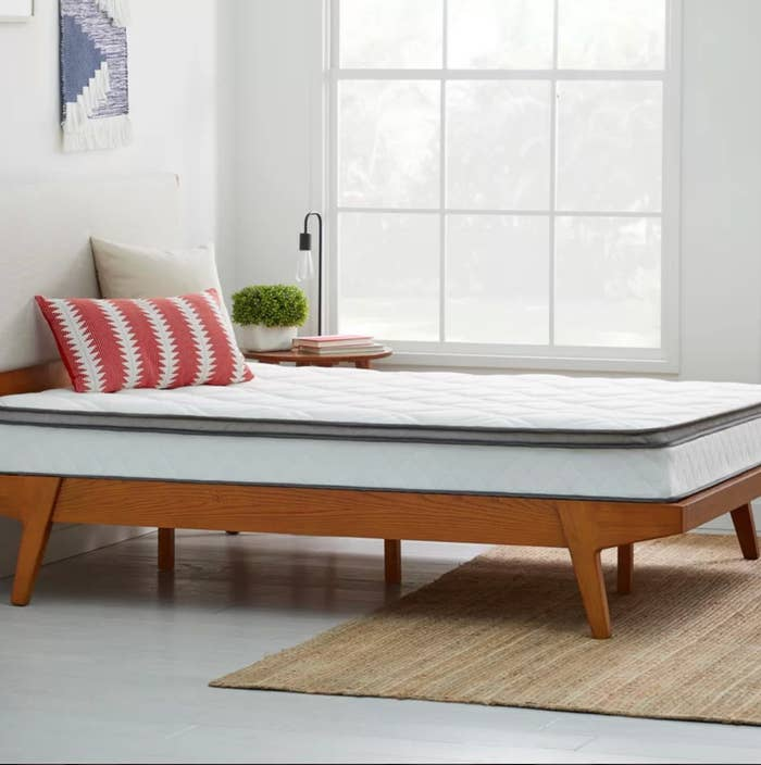 The medium-firm mattress in queen white on top of a wood bedframe