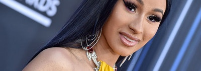 Cardi B posing with jewelry on a red carpet