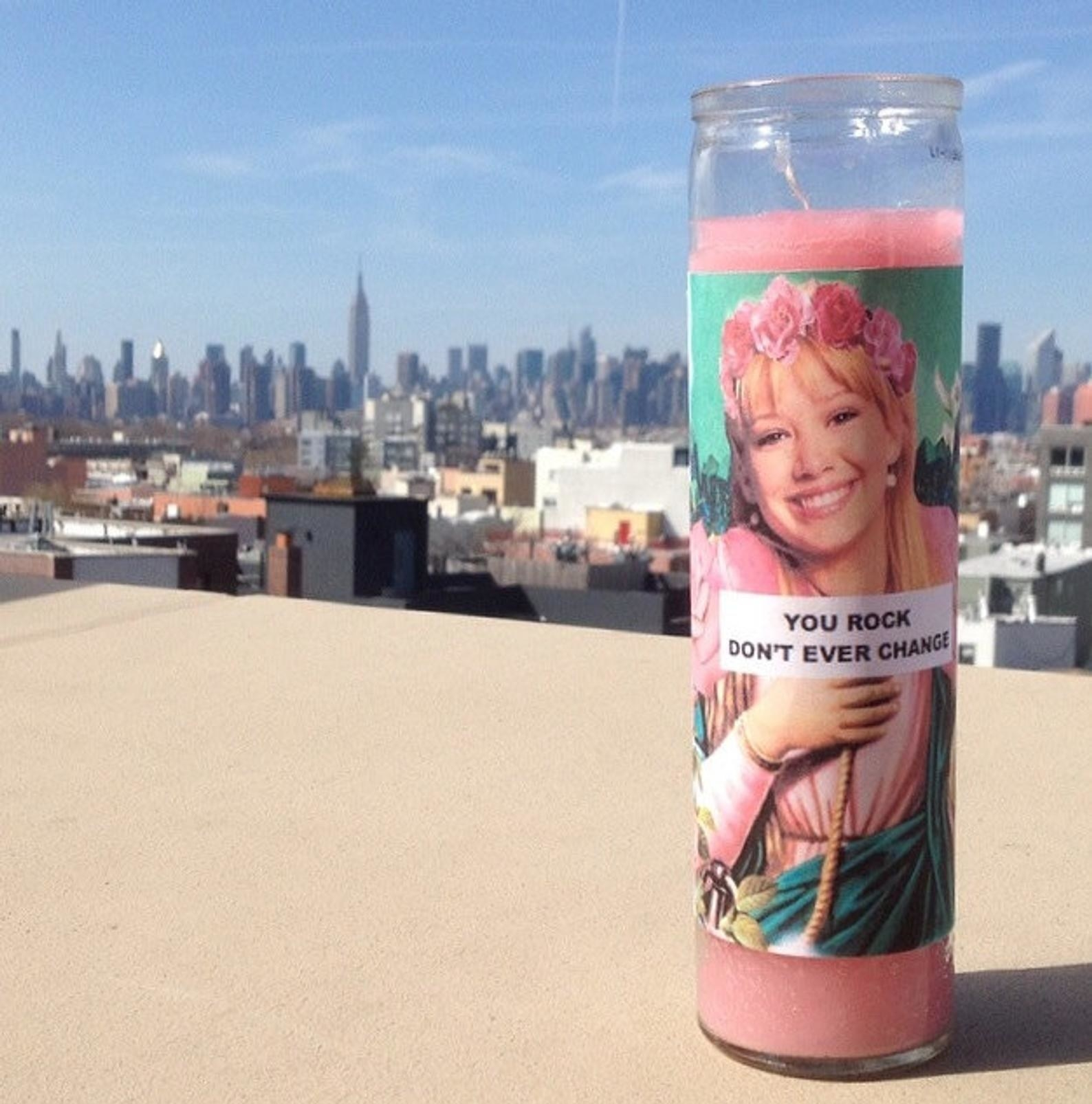 """A tall pink votive candle with a picture of Hillary Duff and the words """"You Rock Don't Ever Change"""" on it"""