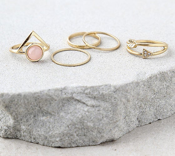 The set of five gold rings; three that are plain, one with a triangle and circular pink stone and one with a double band and an arrow around it