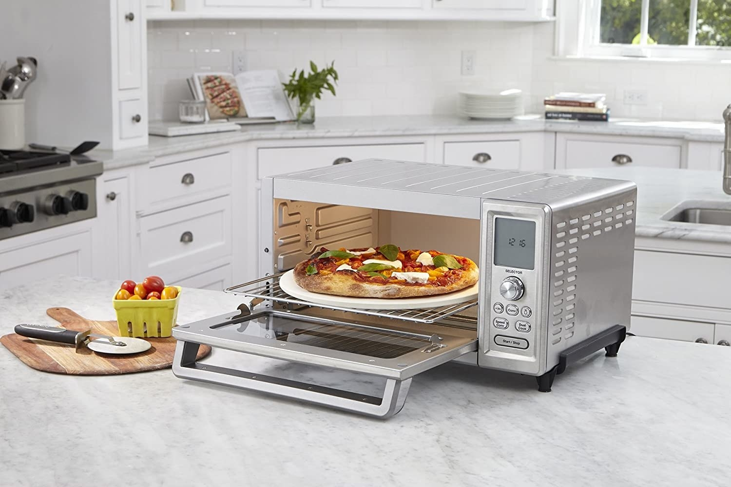 An open toaster with its door open displaying a personal pizza baked to perfection
