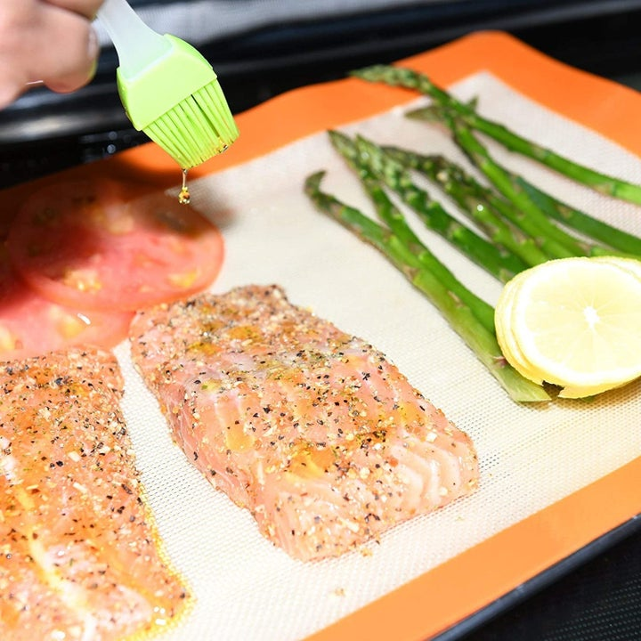 Hand brushes oil over salmon and asparagus placed on an orange baking mat